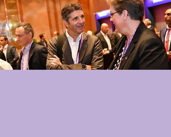 A male and female delegate happily sharing a conversation while networking at an event.