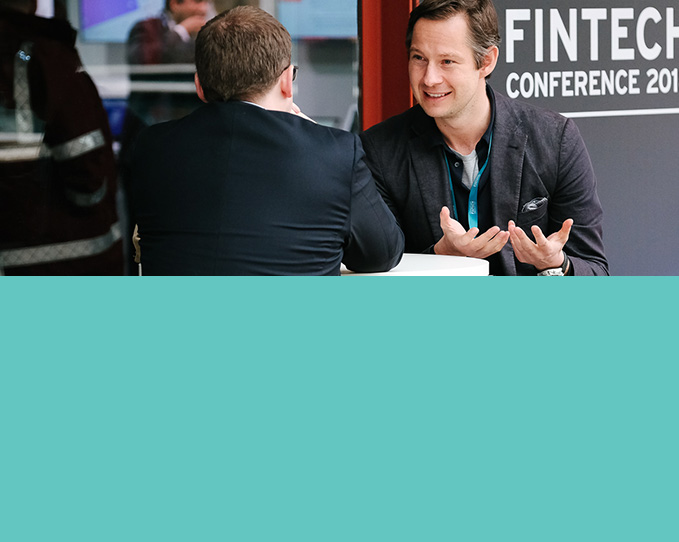 Two male delegates, sat at a table enjoying a conversation at the UK Government International FinTech Conference
