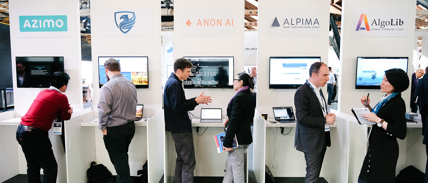 Three pairs having engaging conversations in front of the exhibition stands.