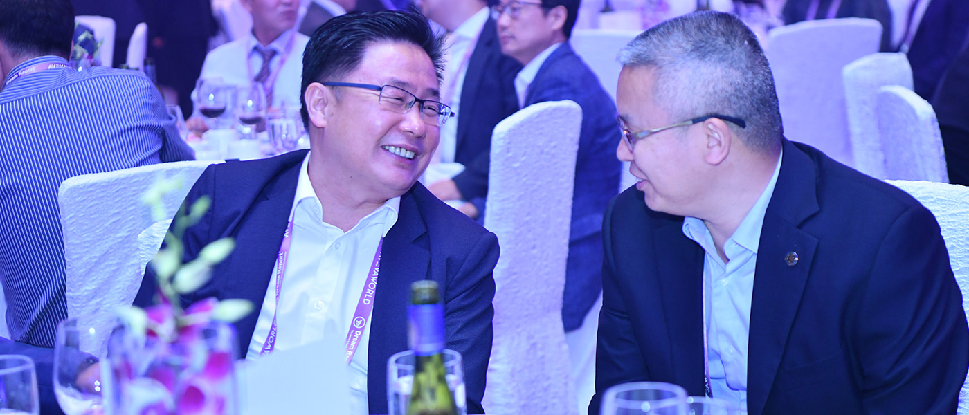 Two men are laughing as they enjoy a bottle of wine at the awards ceremony at the AVEVA World Summit, Singapore event.