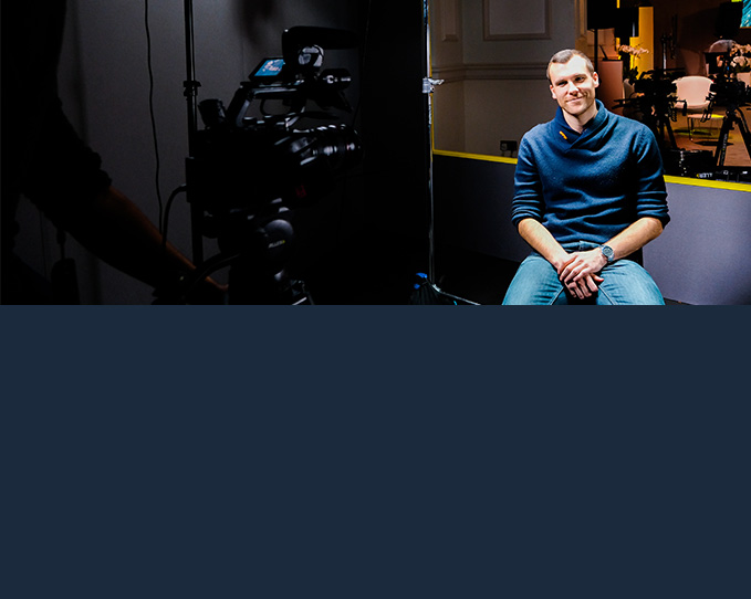 A man sits in front of a camera and camera man as he prepares to go live at the start of his virtual event.
