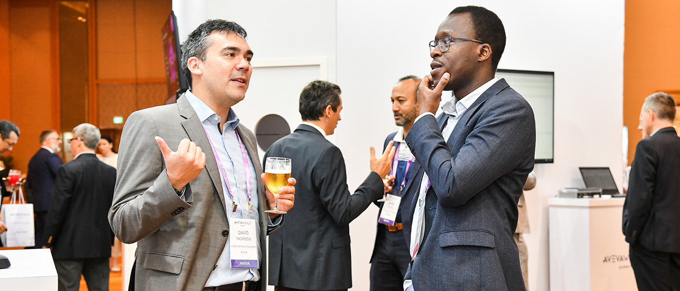 Two men looking engaged in a conversation while networking at the AVEVA World Summit, Singapore.