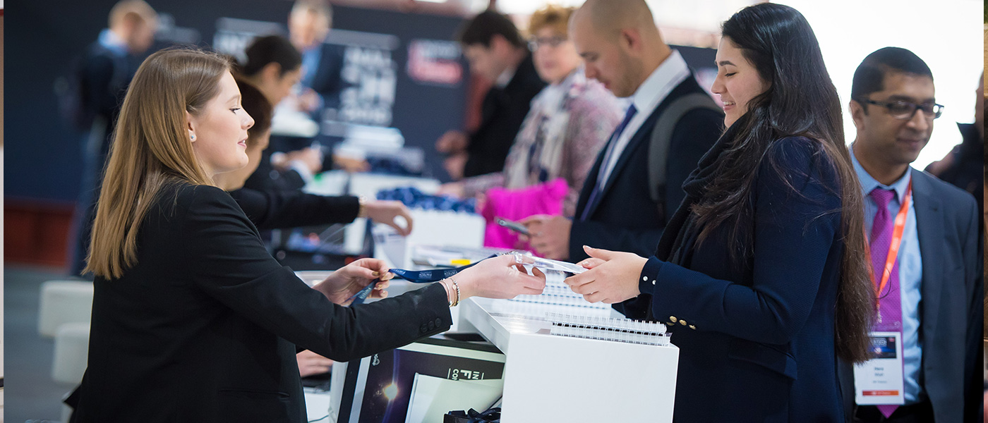 A member of staff handing a delegate their ticket at the registration desk for the UK Government International FinTech Conference.