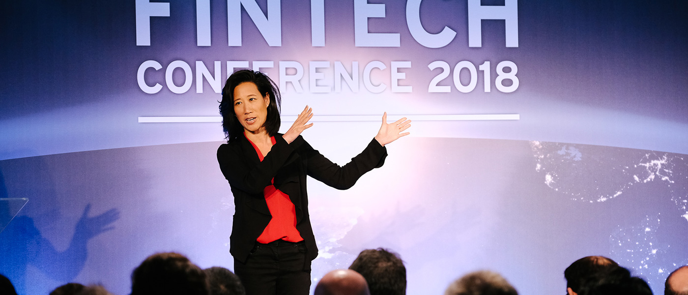 A female speaker, on stage at the UK Government International FinTech Conference.