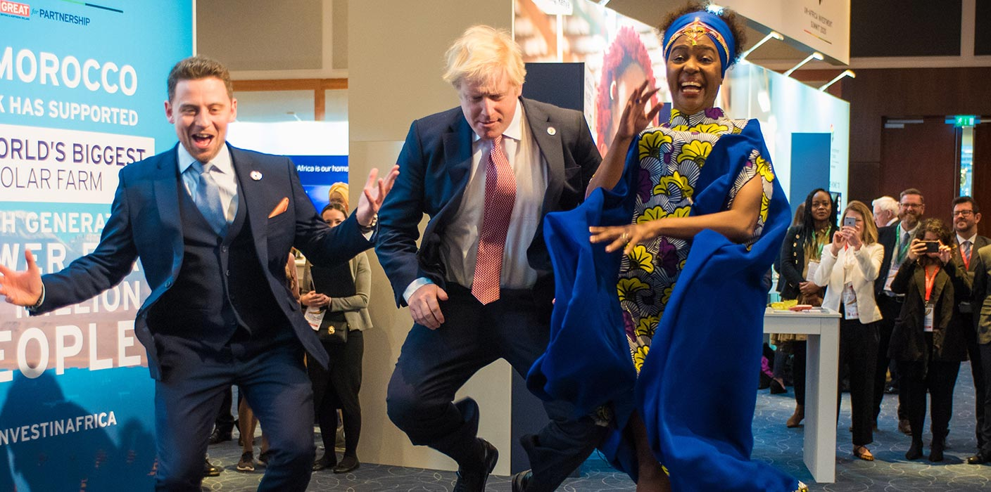 Boris Johnson jumping in the air with two other speakers, among the exhibition stands at the UK Africa Investment Summit 2020.