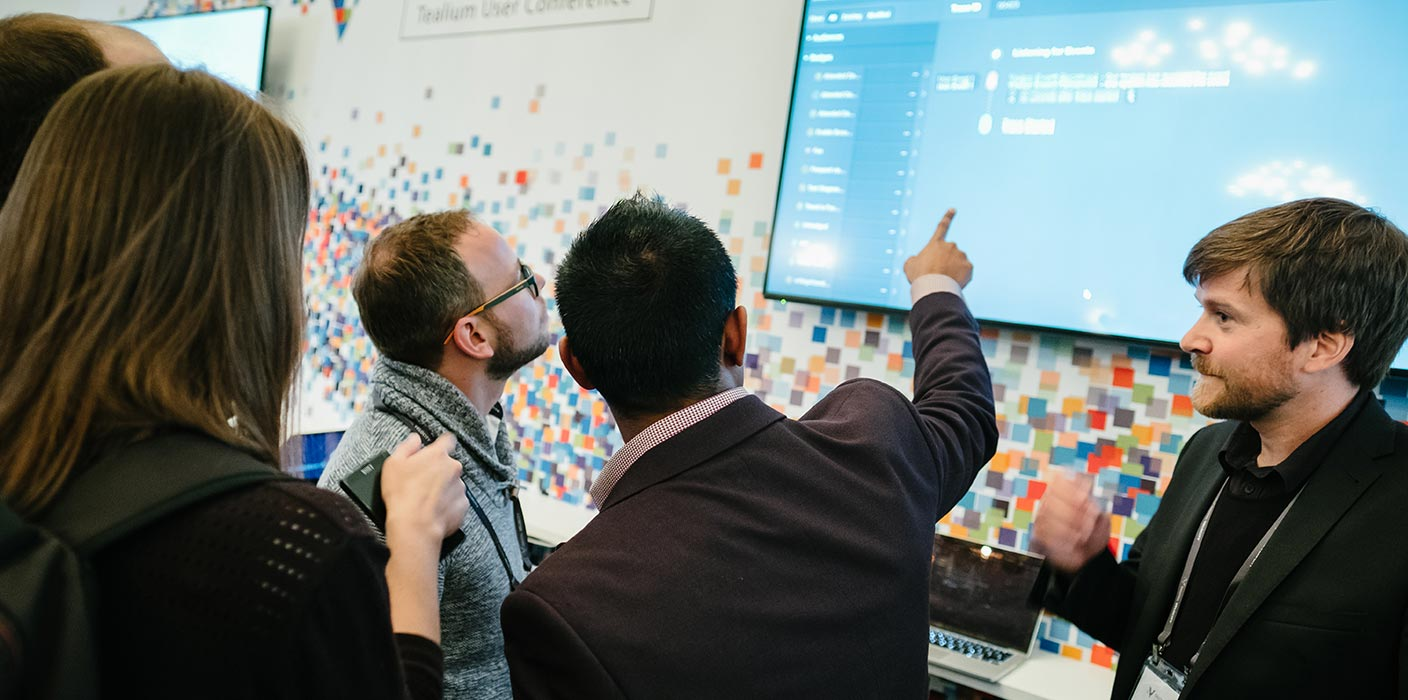 Two delegates are pointing at a screen on an exhibition stand at the Tealium Digital Velocity conference.
