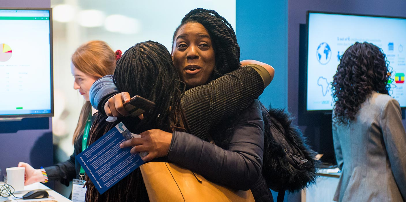 Two female delegates sharing a hug, smiling at the UK Africa Investment Summit 2020.