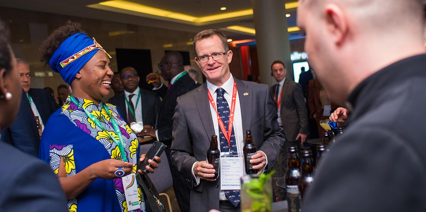 A male and female delegate smiling with a drink in hand at the UK Africa Investment Summit 2020.