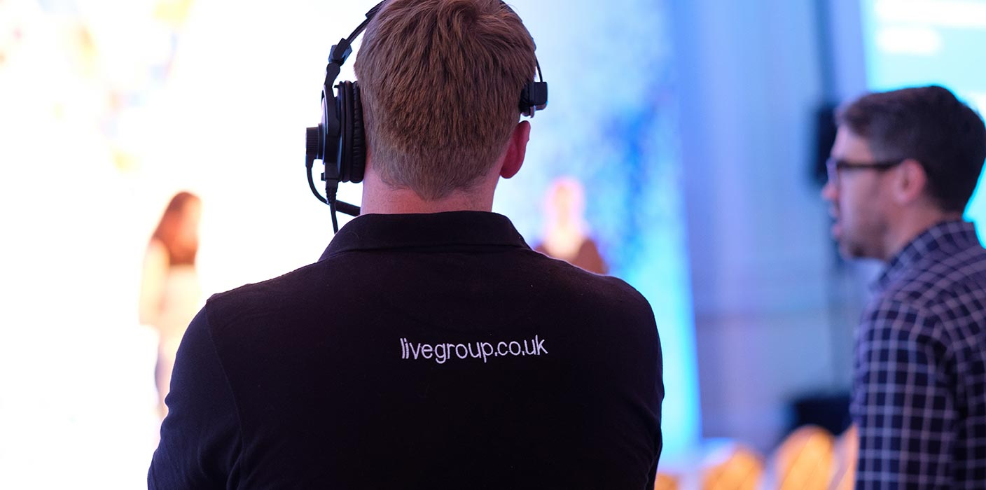 A Live Group team member, wearing a headset, setting up at an event.