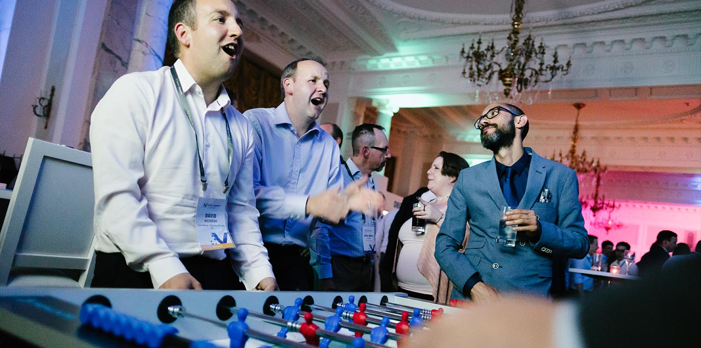 Three male delegates laughing, playing a game of table football with a drink in hand, at a networking event.