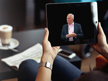 A woman is watching a male speaker on her iPad as she takes part in a Live Group virtual event.