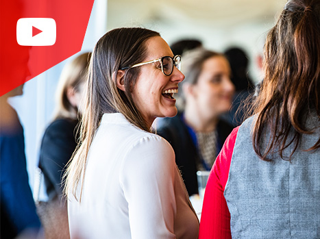 Two female delegates are laughing in the middle of a networking space of an event.